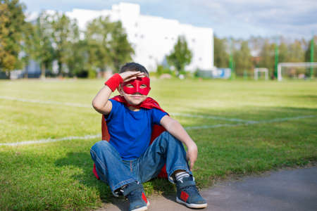 invincible: Boy dressed in cape and mask sitting on grass and looking from under his hand Stock Photo