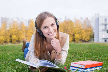 Student listening to headphones, propping head by one hand and holding opened book by other hand
