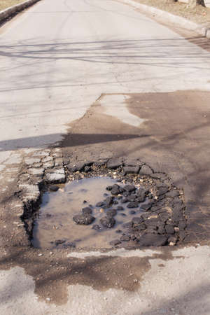 pot hole: Broken asphalt and pot hole on the road