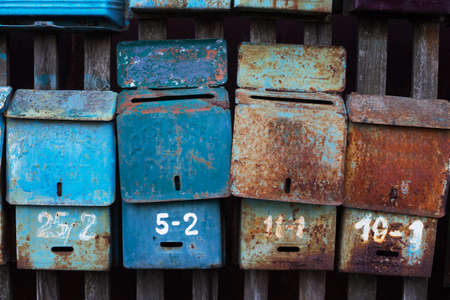 attached: Four old mailboxes with rust attached to the fence