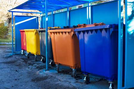 Several colored trash bins under blue plastic canopy Banque d'images