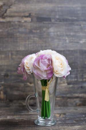 Artificial flower bouquet in vase on wooden background. Vertical imagination