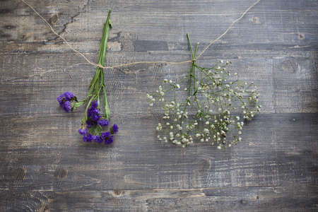 Two flower bunches hanging on string on wooden background