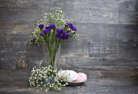 Flowers in vase and zephyrs on saucer on wood background Banque d'images