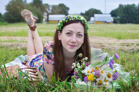 Freckled girl lying on plaid in meadow