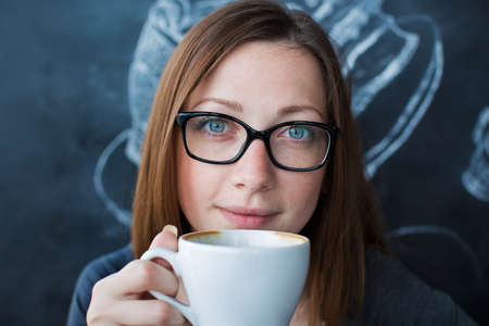 macchiato: Girl holding a cup of coffee and looking at camera