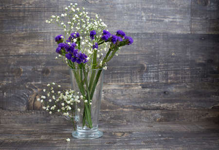 Purple and white flower bouquet in vase on wooden background. Horizontal imagination