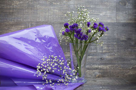 Purple and white flower bouquet in vase and purple packing paper on wooden background. Horizontal imagination