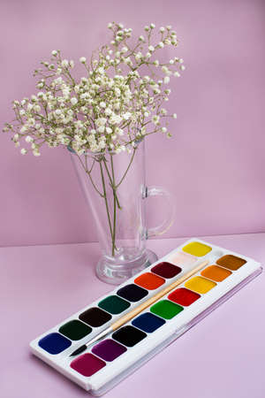 Sprigs of gypsophilas in vase and watercolor paints on pink background. Vertical imagination