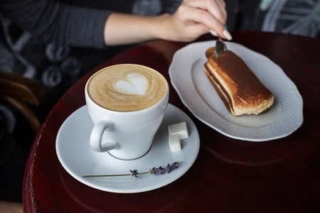 A cup of coffee with foam and a tiramisu cake on the table