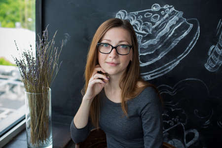 Young woman in glasses and gray dress sitting in cafe