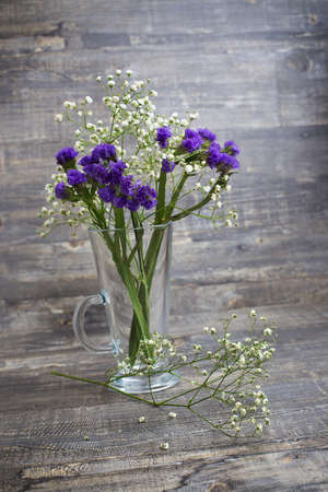 Purple and white flower bouquet in vase on wooden background. Vertical diagonal imagination