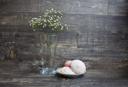 White flower in vase and two white zephyrs on saucer on wood background Banque d'images