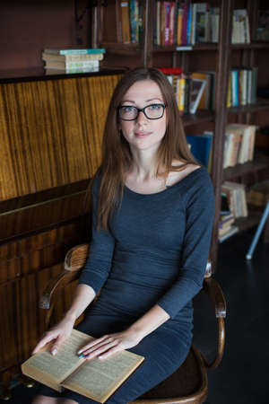 Young woman in glasses and with open book sitting on chair in cafe