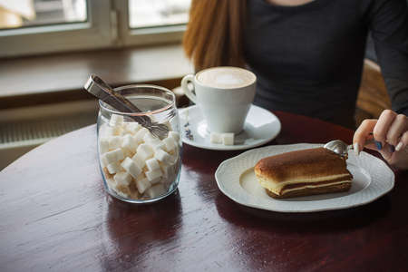 A jar of sugar, a cup of coffee with foam and a tiramisu cake on the table