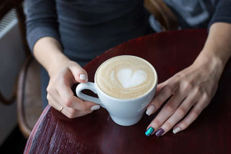 Women's hands holding a cup of coffee with foam and heart