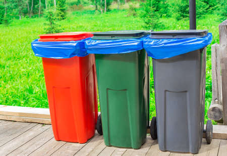 Three garbage cans with blue plastic bags standing on wooden floor on nature background