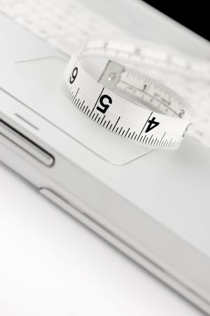 Measuring tape on keyboard of white laptop. Copy space. Shallow Dof. Online dieting concept. Stock Photo