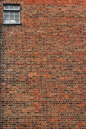 red brick wall with small window in left corner