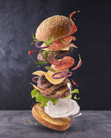 Delicious burger with flying ingredients on dark concreate background