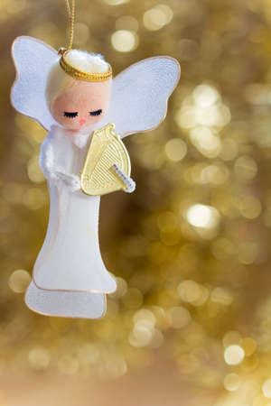 angel figurine: Angel with a Harp on a Golden Background with Copy Space, Selective Focus