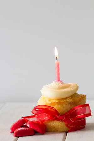 vanilla cupcake: Vanilla Cupcake with Red Ribbon, Red Chocolate Hearts and Burning Candle