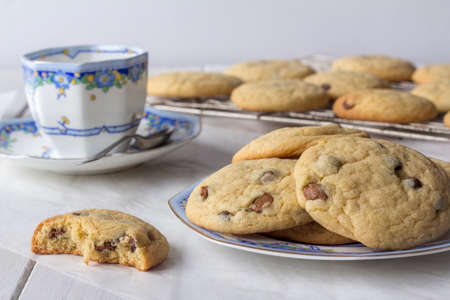 eaten: Fresh Homemade Chocolate Chip Cookies with Tea and One Partly Eaten on White Wooden Table Stock Photo