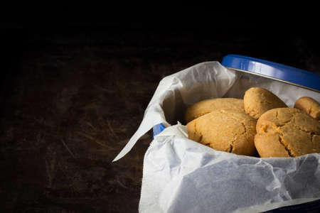 gingernuts: Gingernuts in a Blue Tin on a Dark Background Horizontal with Copy Space Left Stock Photo