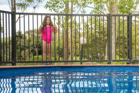 Pool-Sicherheit - junges Mädchen, das den äußeren Pool-Zaun schaut herein steht, um Northland New Zealand zu vereinigen