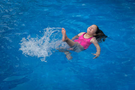 Young Girl Floating in Pool Making Splash with Her Legs