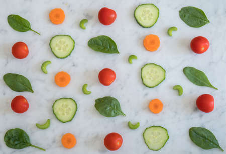 Pattern of Salad Ingredients on Marble Bench Top, Baby Spinach Leaves, Carrot, Cherry Tomatoes, Celery and Cucumber