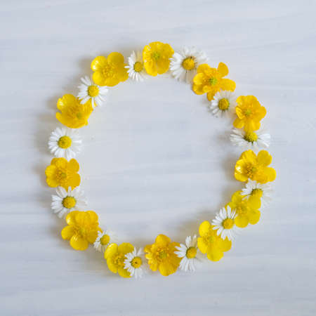 Daisy and Buttercup Wreath of Flowers on White Wooden Background with Copy Space - Flat Lay