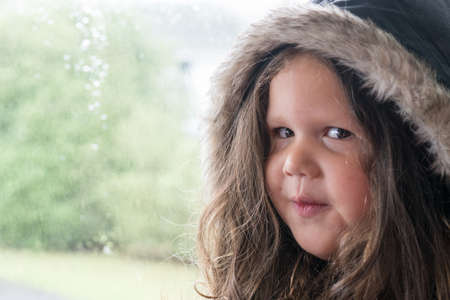 Portrait of Young Mixed Race Girl with Cheeky Look in Front of Window on Rainy Day with Her Coat on Ready to Go Out