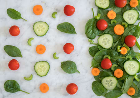 Pattern of Salad Ingredients on Marble Bench Top, Baby Spinach Leaves, Carrot, Cherry Tomatoes, Celery and Cucumber Made into Salad on One Side  Reklamní fotografie