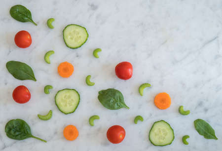 Pattern of Salad Ingredients on Marble Bench Top, Baby Spinach Leaves, Carrot, Cherry Tomatoes, Celery and Cucumber with Copy Space