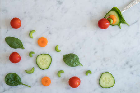 Pattern of Salad Ingredients on Marble Bench Top, Baby Spinach Leaves, Carrot, Cherry Tomatoes, Celery and Cucumber with a Combination of them on a Fork with Copy Space