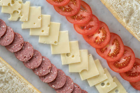 Rows of Cheese, Salami and Tomato Between Bread Ready to Be Made into A Sandwich from Above on a Diagonal