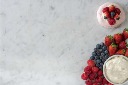 Meringue Beside a Selection of Raspberries, Strawberries, Blueberries and Cream on Marble Table Top from Above with Copy Space Reklamní fotografie