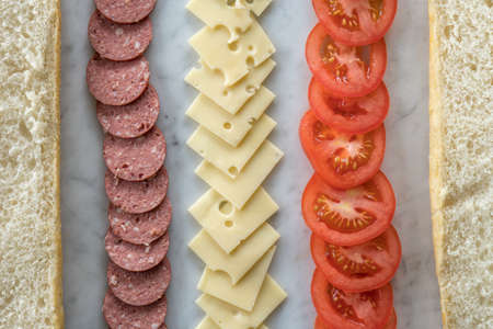 Rows of Cheese, Salami and Tomato Between Bread Ready to Be Made into A Sandwich from Above  Reklamní fotografie