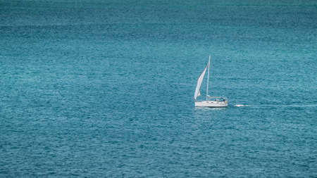 Yacht Sailing Across a Blue Ocean on Bright Summers Day