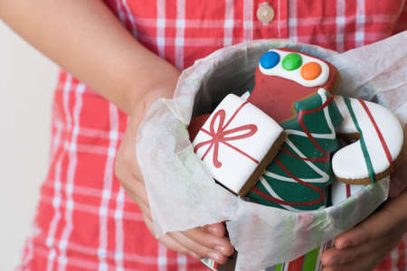 Close Up of Young Boy Offering Tin of Christmas Gingerbread Cookies as Gift Reklamní fotografie