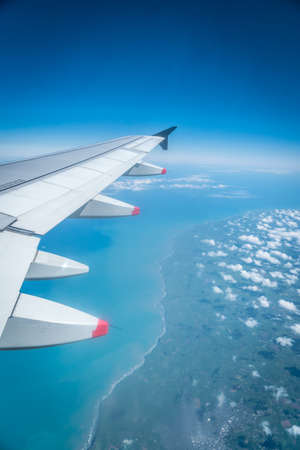 View from airplane window with wing flying over coastline and ocean with clouds, West Coast, North Island, New Zealand