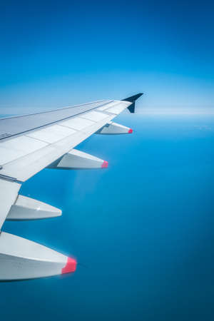View from Airplane Window with Wing Flying over Ocean on a clear Day Reklamní fotografie