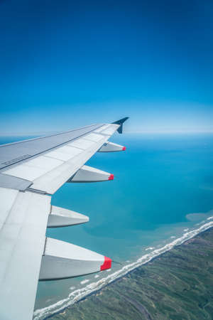 View from airplane window with wing flying over coastline and ocean, West Coast, North Island, New Zealand Reklamní fotografie