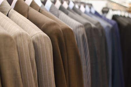 traje formal: Trajes de hombre colgando en una tienda de ropa.
