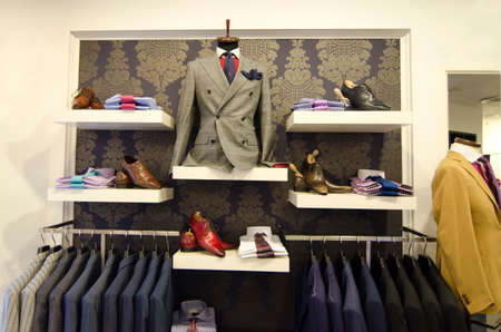 Men suits ans shoes hanging in a luxury clothing store. Stock Photo