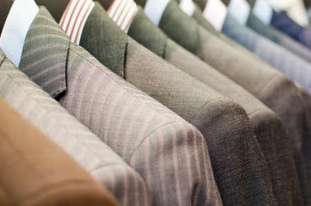 衣料品店にぶら下がっている男性スーツ。 写真素材