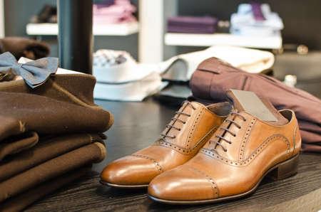 shoe store: Zapatos, camisetas y otras prendas de vestir en una tienda de moda de los hombres.