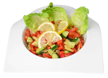 exotically: Vegetable salad with cucumber, tomatoes, lemon, pepper and salad leaves, isolated on a white . Stock Photo