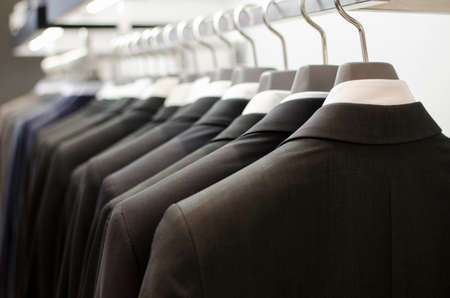 Men suits hanging in a clothing store. Stock Photo